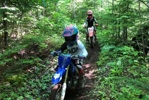 Kids trail riding through woods