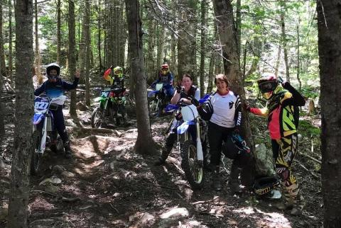 Women dirt bike riders in woods